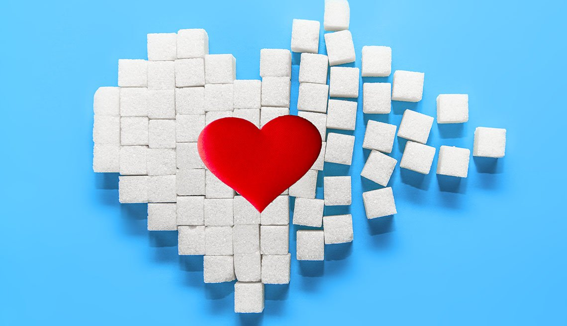 Red heart on heart made of sugar cubes on a blue background.
