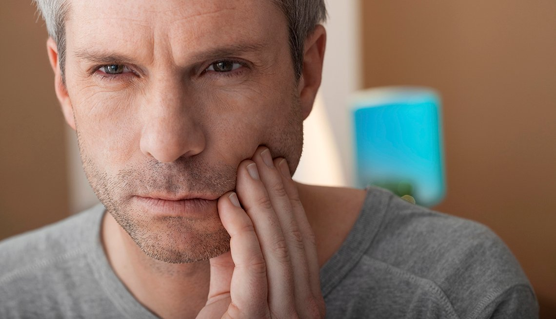 Man holding his jaw, looking like he is having tooth pain