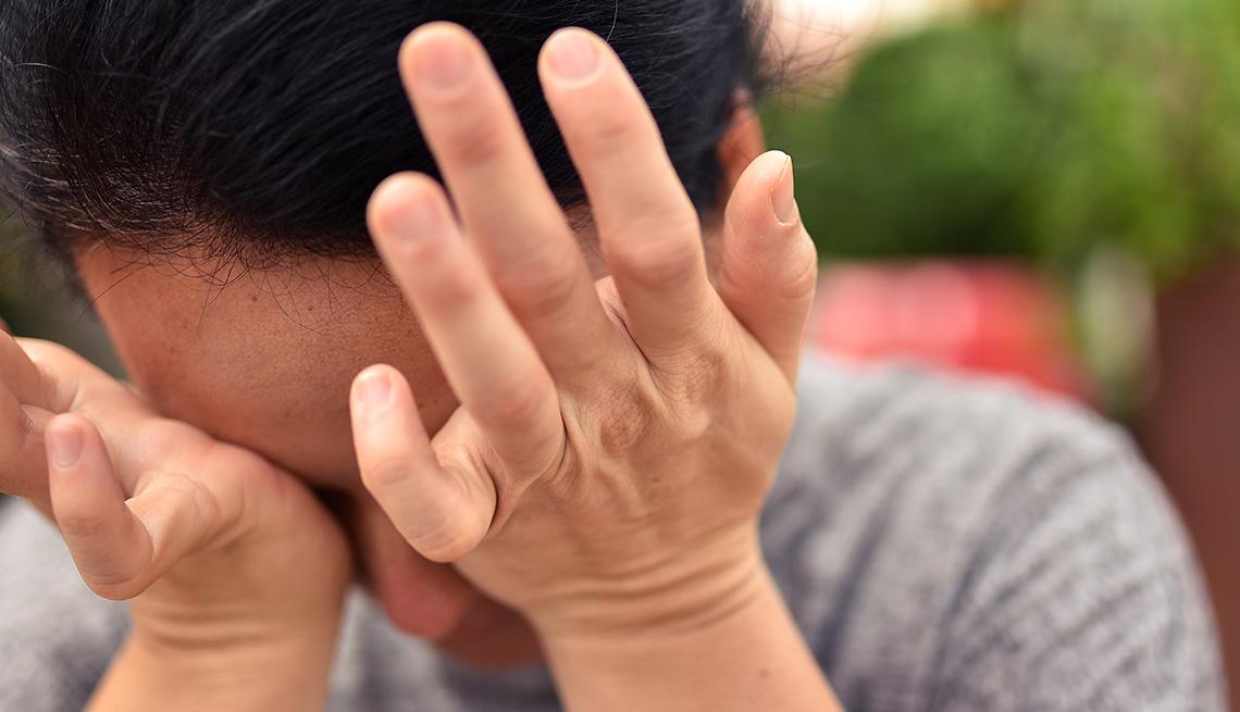 Una mujer se frota los ojos con ambas manos