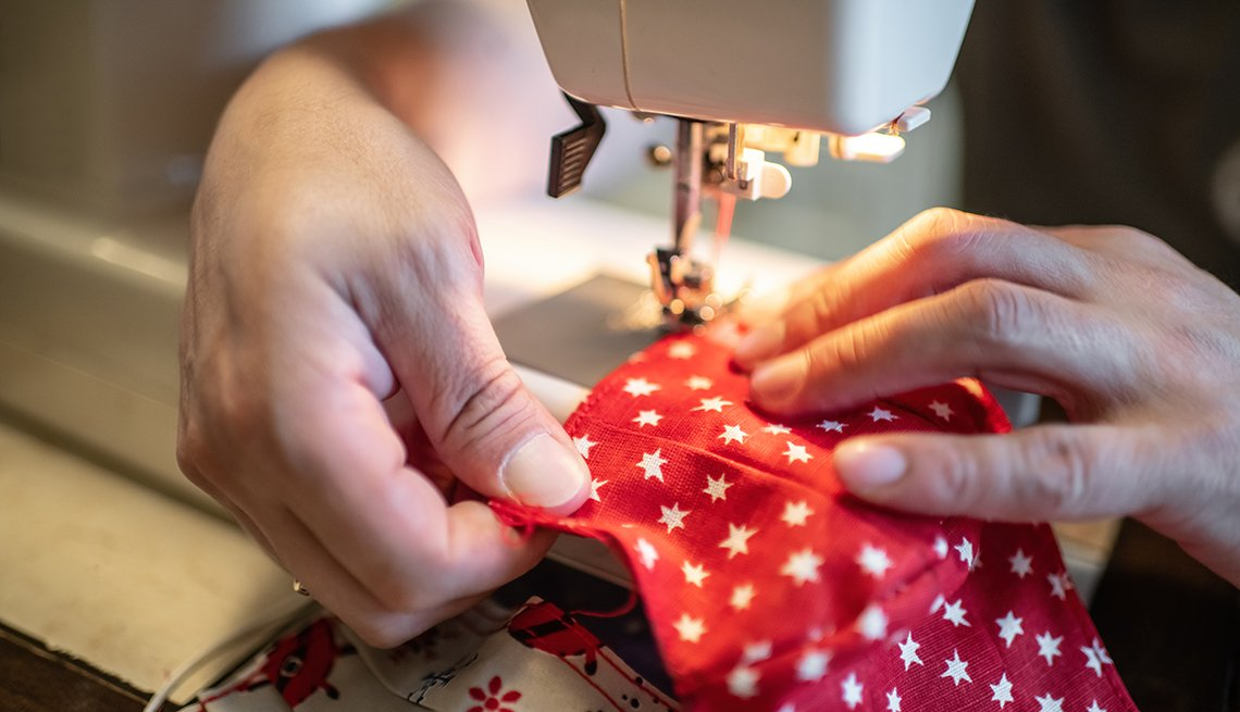 close up of person sewing a face mask
