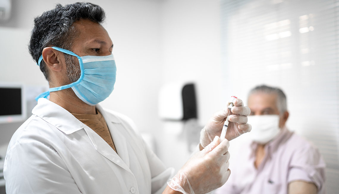 medical provider preparing vaccine with patient in background