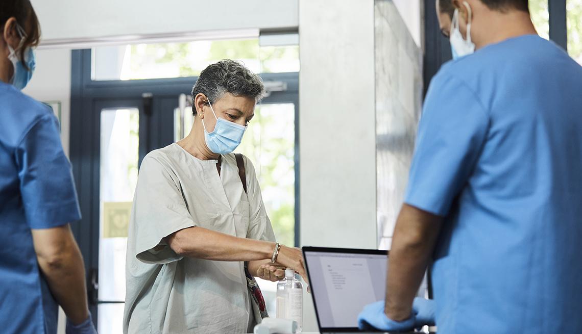 Una mujer se pone desinfectante en las manos mientras dos enfermeros la observan