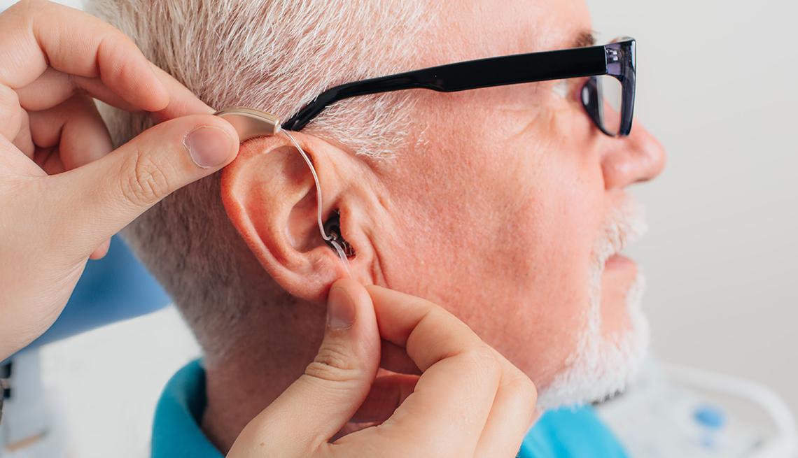 Un médico pone un pequeño audífono inteligente en el oído de un hombre