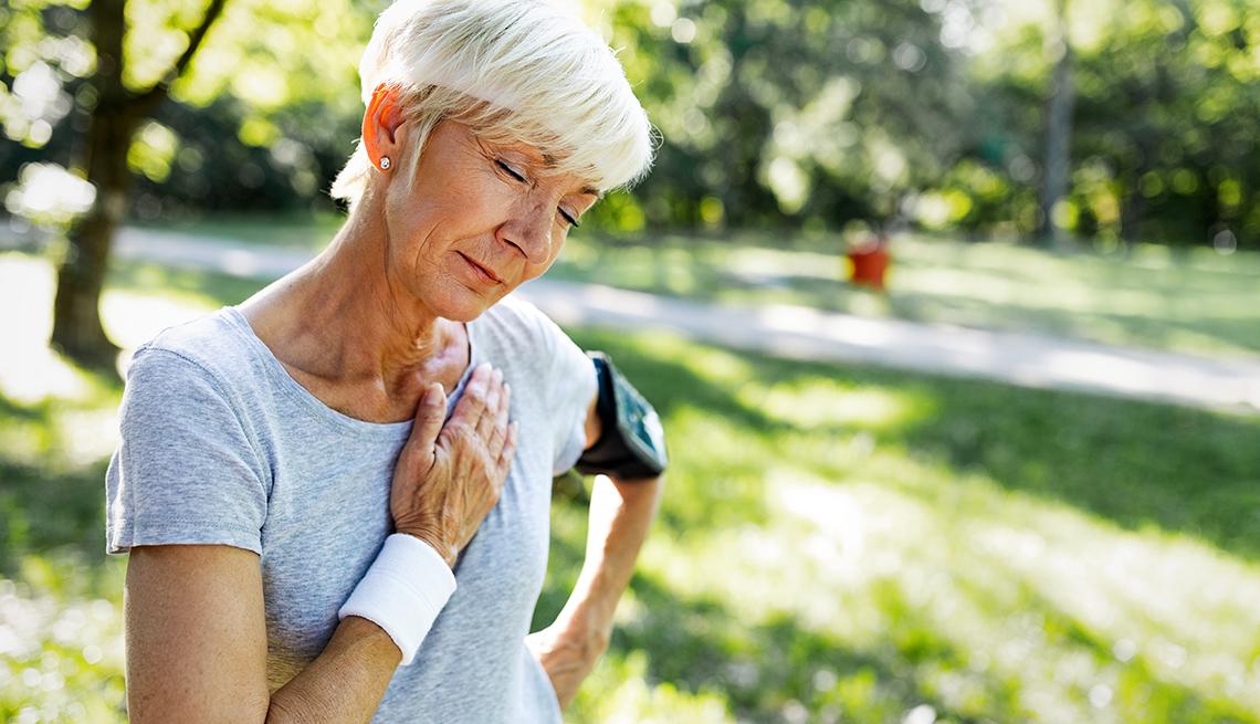 Una mujer, que se ejercita al aire libre, se detiene y se toca el pecho en señal de dolor.