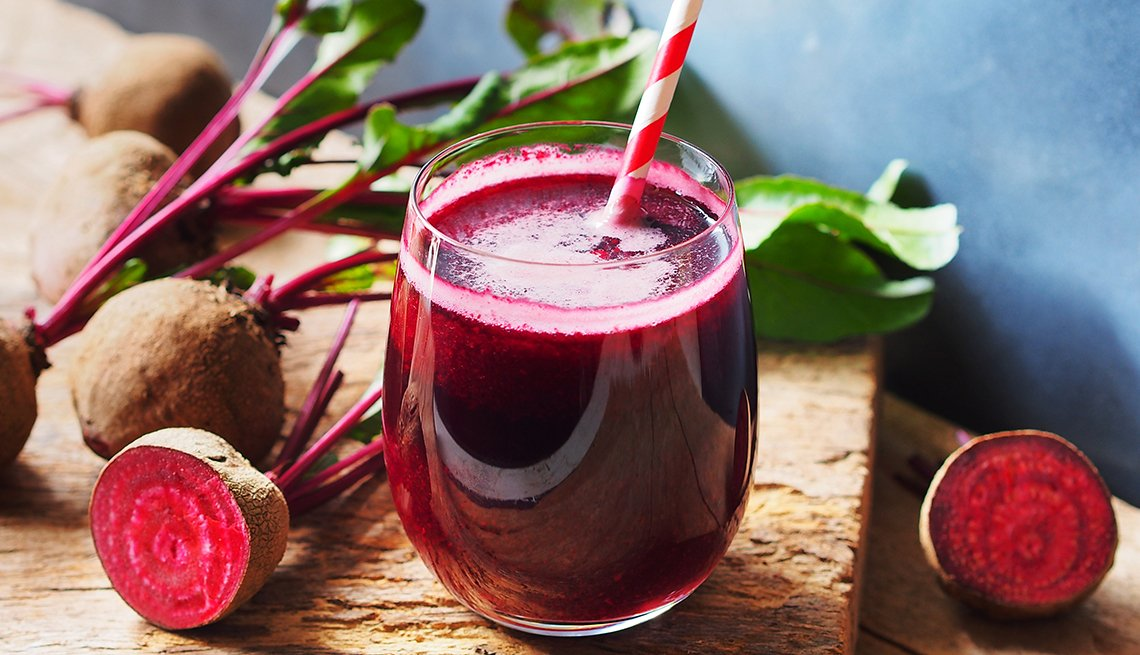 Glass of beet juice surrounded by beets.