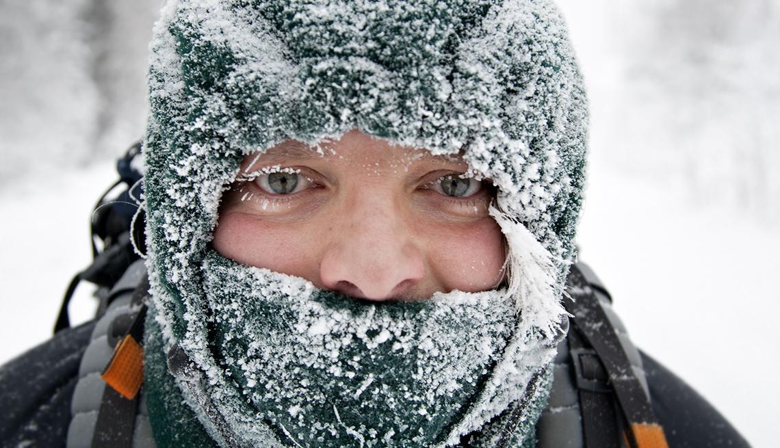 Toma cercana de un hombre bien abrigado y cubierto de nieve