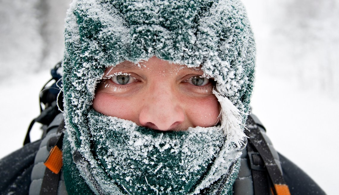 a close-up of a mans face, with frosty eyelashes, wearing a snow covered balaclava, winter background