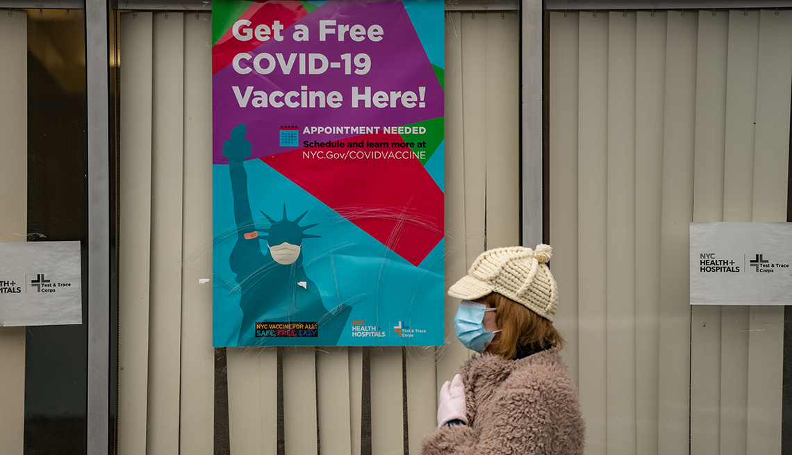 A woman wearing a face mask stands outside a COVID-19 vaccination site in New York City.