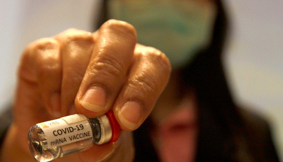 A researcher holds a COVID-19 mRNA vaccine