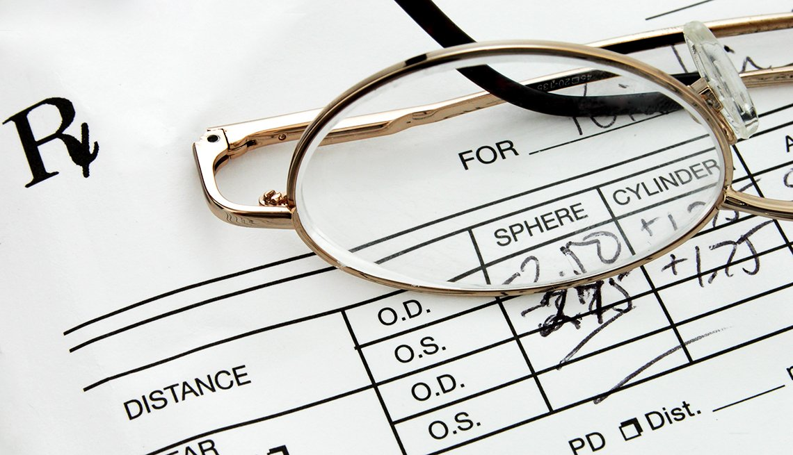 Close up of a pair of eyeglasses sitting on top of an eyeglass prescription.