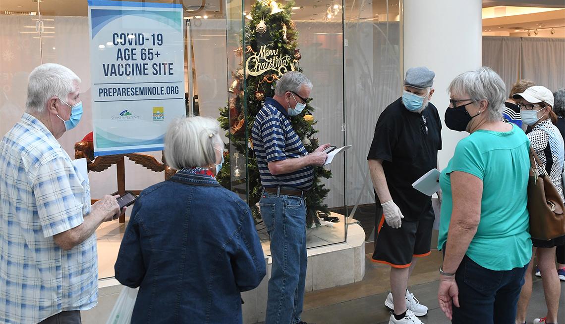 Un grupo de personas mayores esperan en una fila en la víspera de Año Nuevo para recibir una vacuna COVID-19 en una tienda desocupada en el Oviedo Mall en Oviedo, Florida.