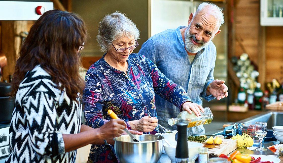 Tres adultos cocinan juntos