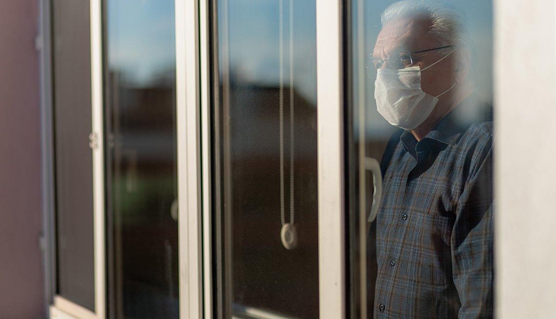 Un hombre con mascarilla mira por una ventana