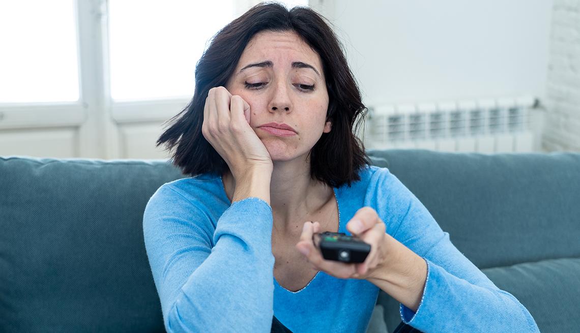 Mujer sentada en el sofá cambiando de canal de TV