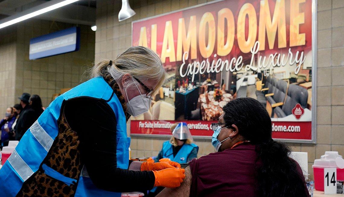 item 3 of Gallery image - a healthcare worker administers a covid vaccine to a woman inside the alamodown stadium in texas
