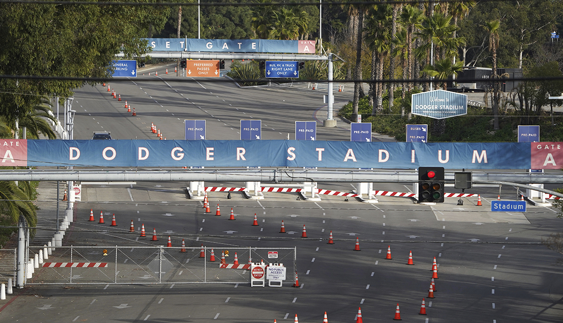 an entrance to dodger stadium parking lot arranged for lines of cars to wait their turn for the covid vaccine