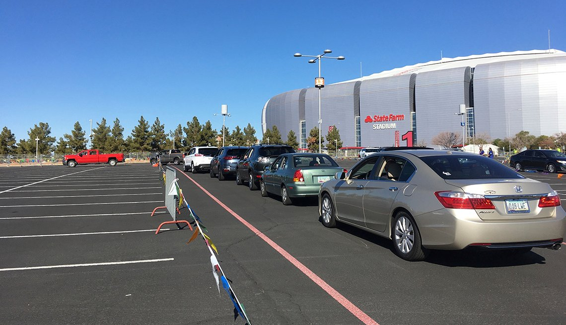 item 8 of Gallery image - drivers wait in their cars in line for the covid vaccine at state farm stadium in glendale arizona