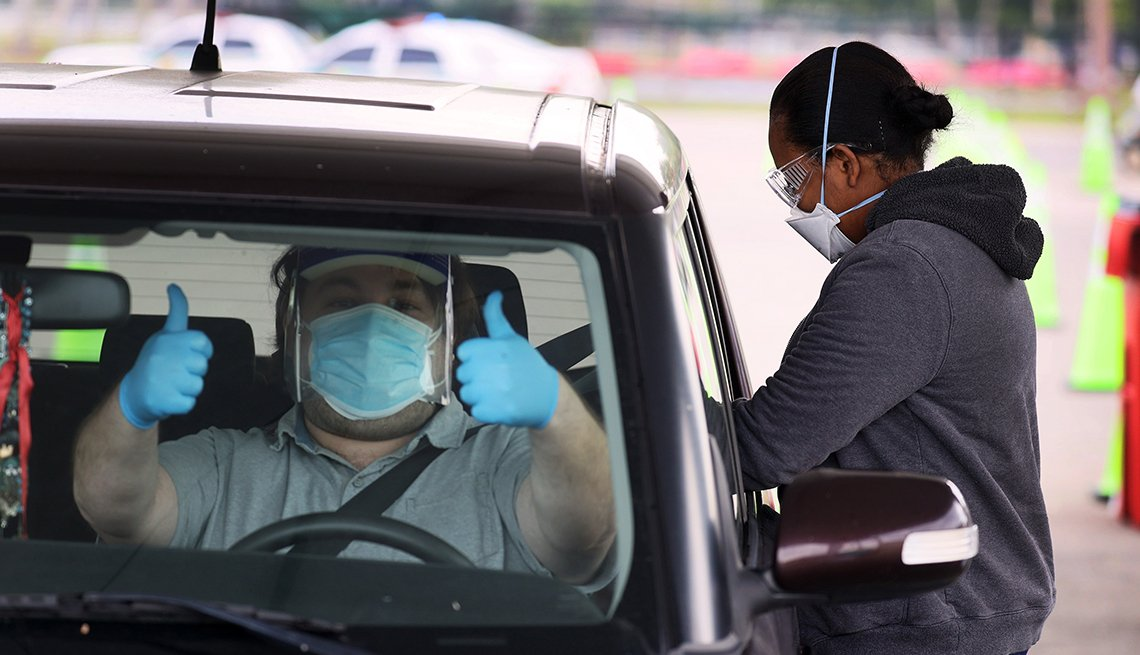 item 6 of Gallery image - a driver in protective gear give a thumbs up from inside his car at the vaccination site in tropical park in miami florida