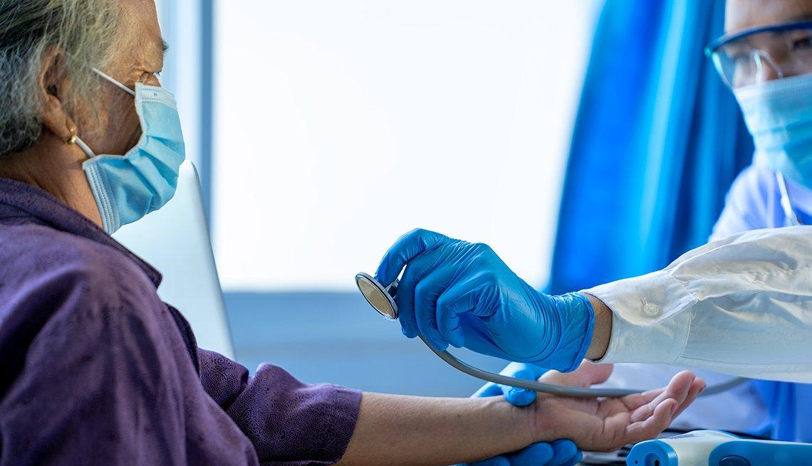 Un médico examina el pulso y la presión de una mujer
