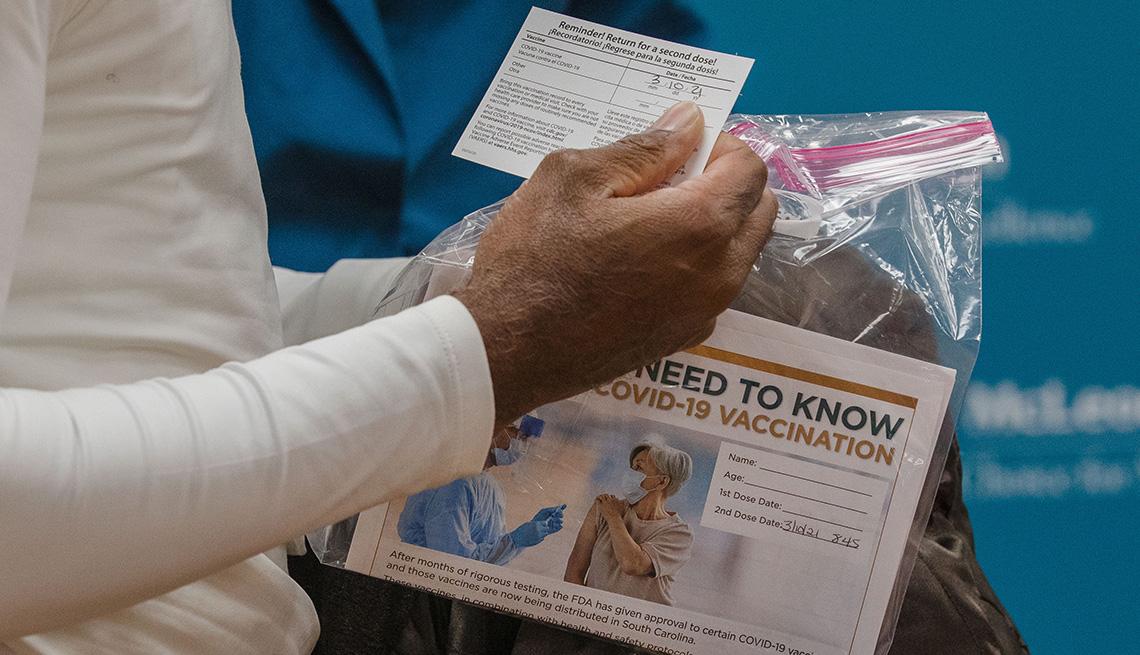 Un paciente sostiene una tarjeta de vacunación y un paquete de información después de recibir la vacuna contra la COVID-19