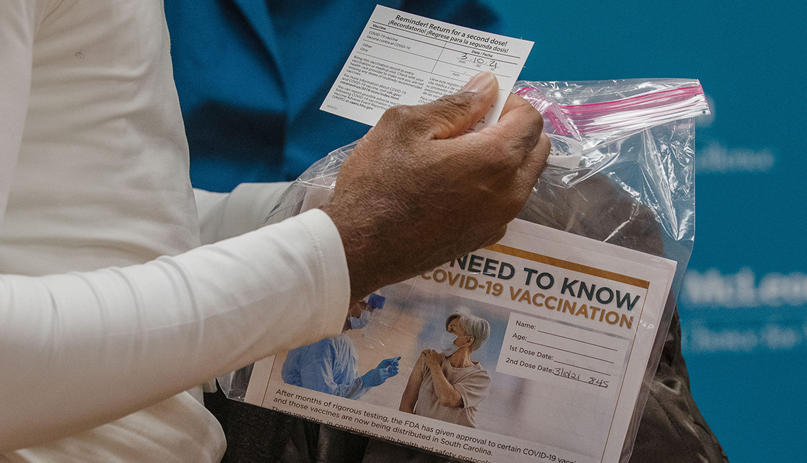 A patient holds a vaccination card and information packet after receiving the Pfizer-BioNTech vaccine