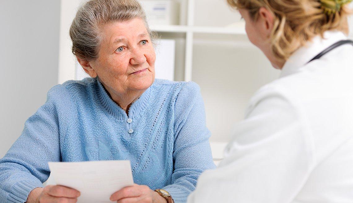Una mujer sostiene un papel con preguntas para su doctora