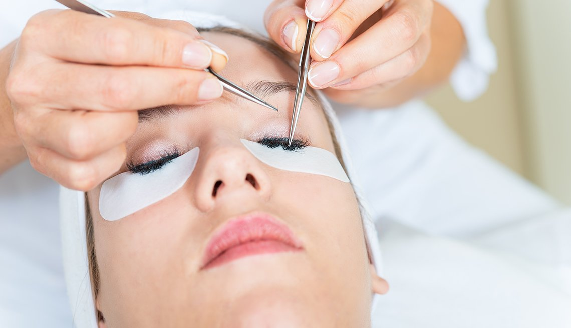 Woman getting eyelash extensions put on