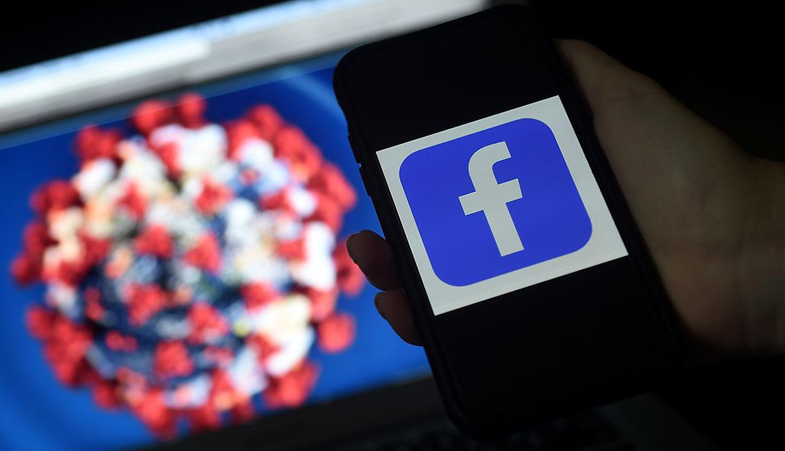 facebook logo on phone in front of a coronavirus illustration