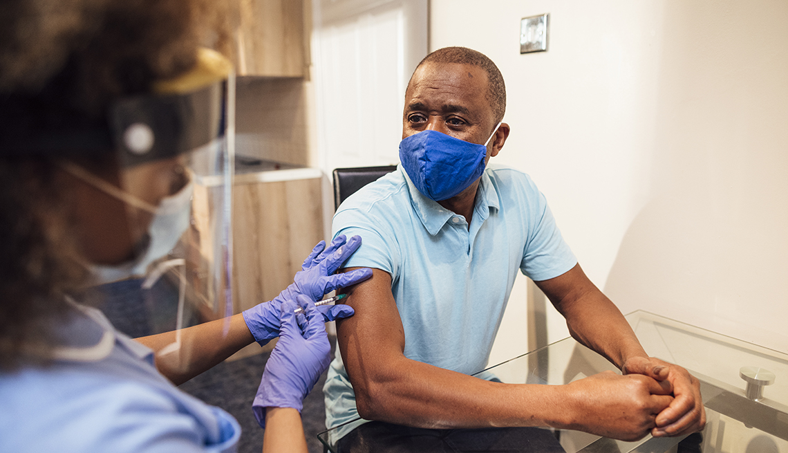 A nurse gives an African American man the coronavirus vaccine. Both are wearing face masks