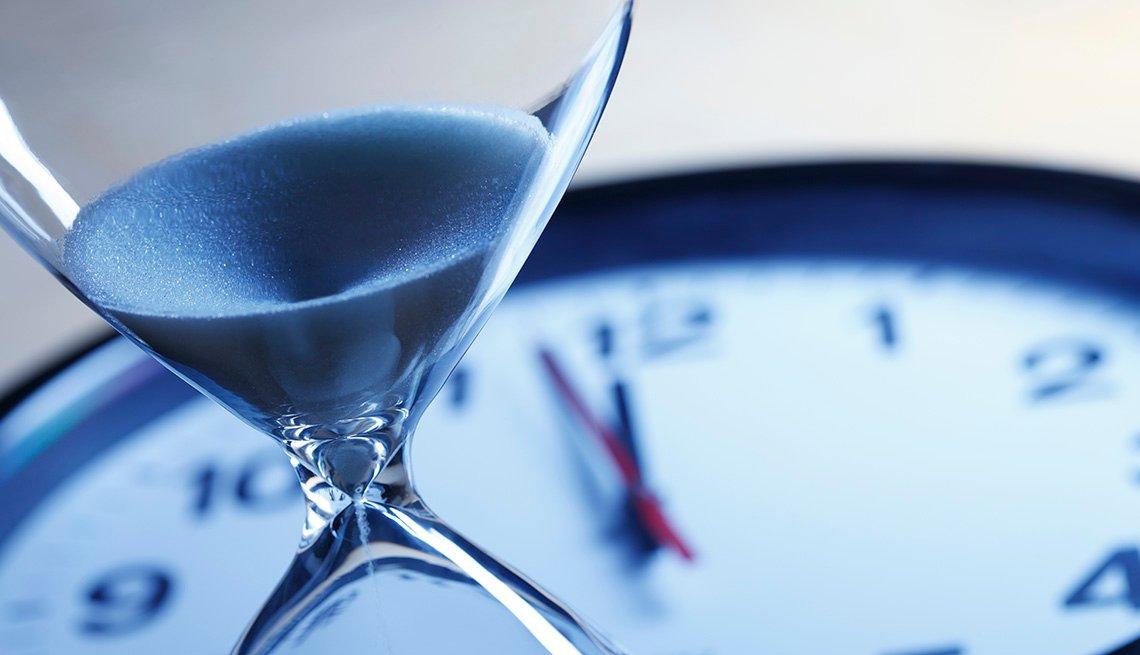Reloj de arena y reloj con manecillas que apuntan las 12