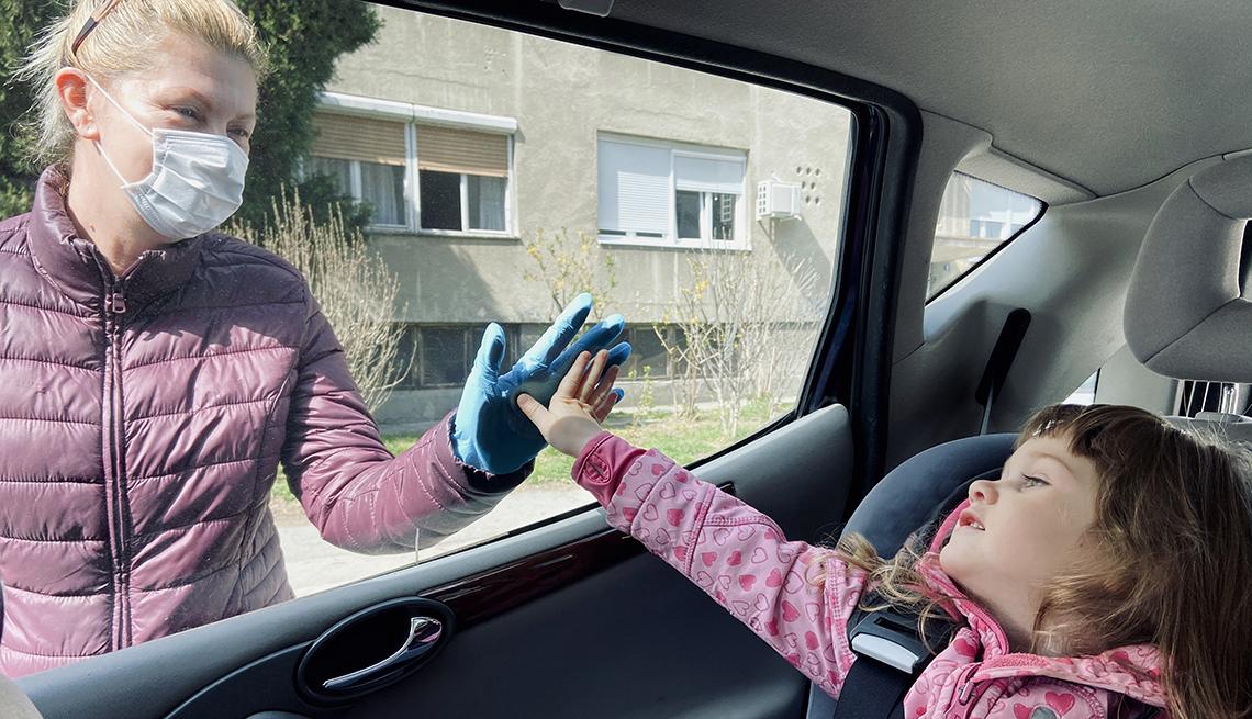 Woman touching her grandchild's hand through a car window, wearing a face mask