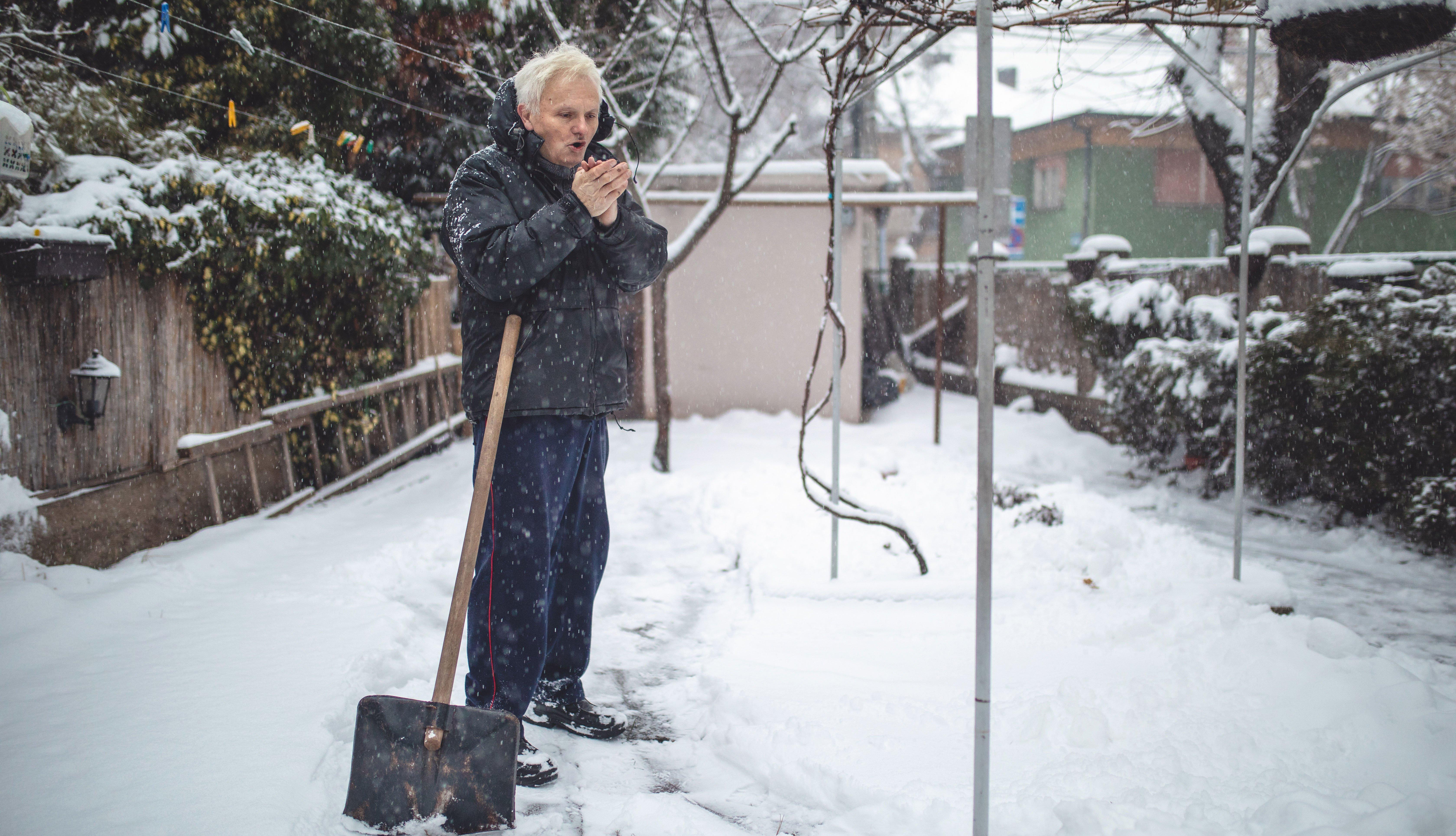 Un hombre adulto mayor saca nieve con una pala