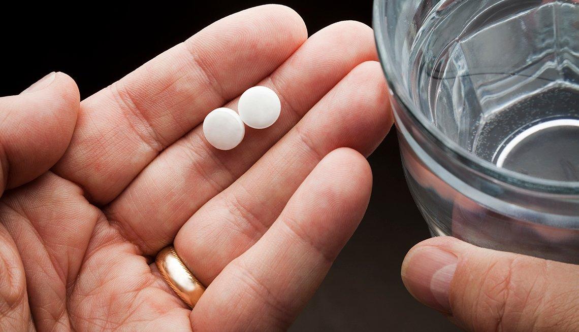 Un hombre sostiene unas pastillas en una mano y un vaso de agua en la otra