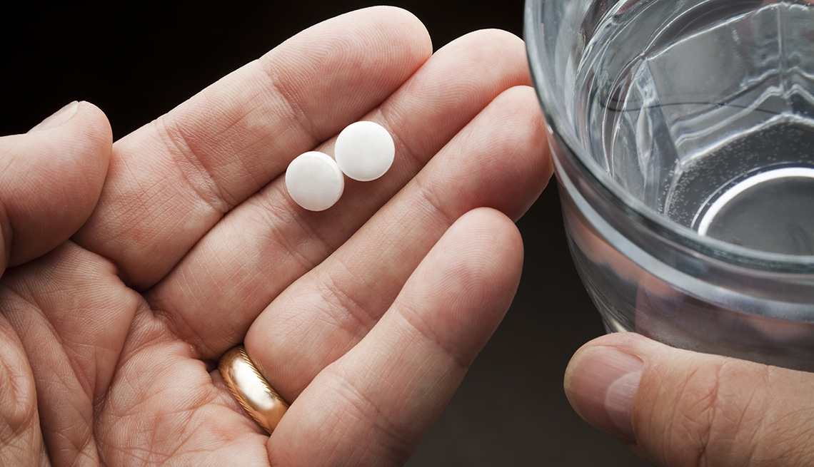 man's hands holding pain pills and a glass of water