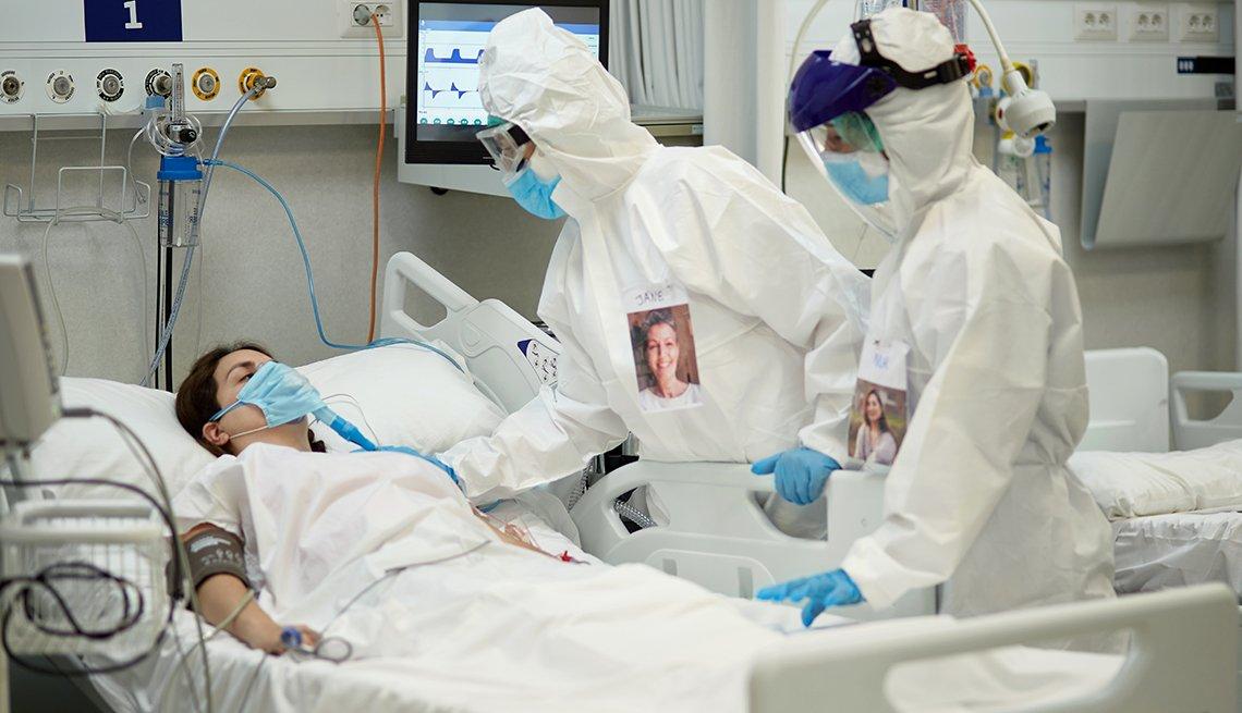 Paciente con COVID-19 acostado en una cama de hospital y personal médico que lo atiende