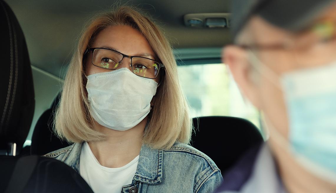 Una mujer en un taxi con una mascarilla