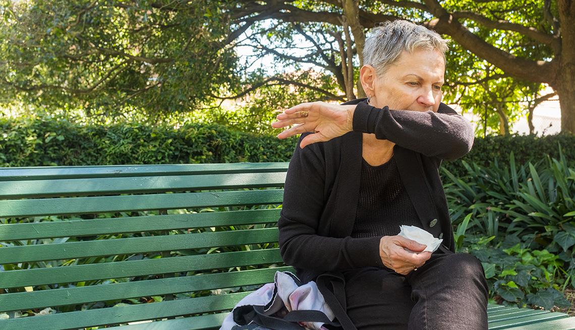 Una mujer, sentada en un banco, tose en su codo