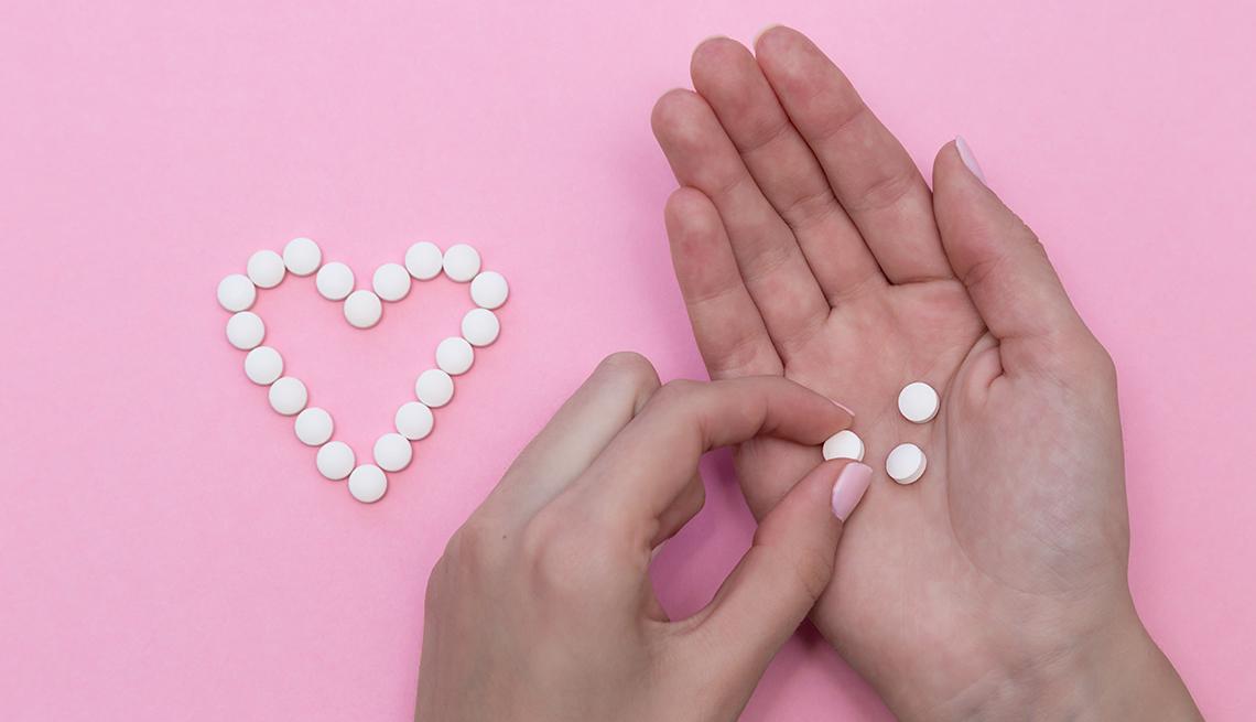 Manos de una mujer sostienen unas pastillas, sobre un fondo rosa con pastillas formando un corazón