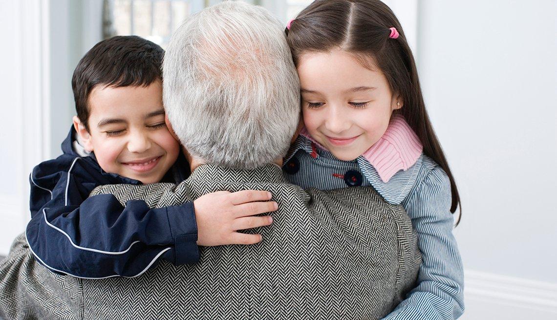 Un abuelo abraza a sus dos nietos