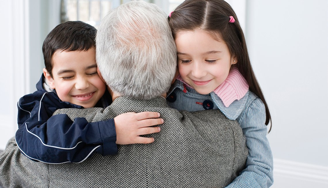 Grandchildren hugging their grandfather.