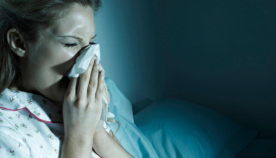 Una mujer se cubre la boca y nariz con un pañuelo mientras estornuda