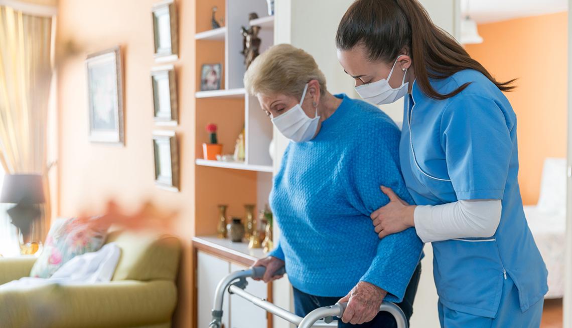 Una enfermera ayuda a la residente de un hogar a desplazarse con un andador