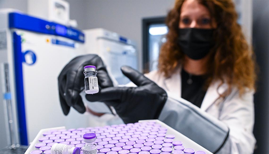 a healthcare technician unfrosts vials of a covid vaccine in a lab