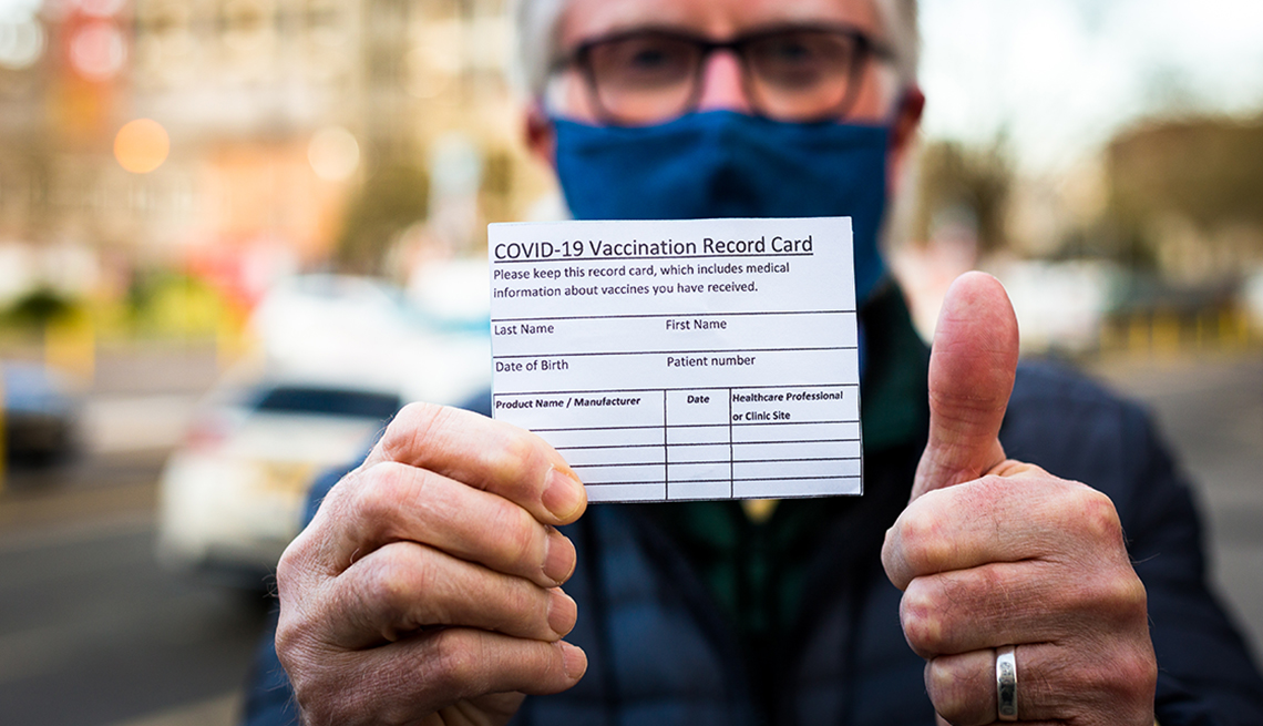 A man holding his vaccination record card and giving the thumb's up sign.