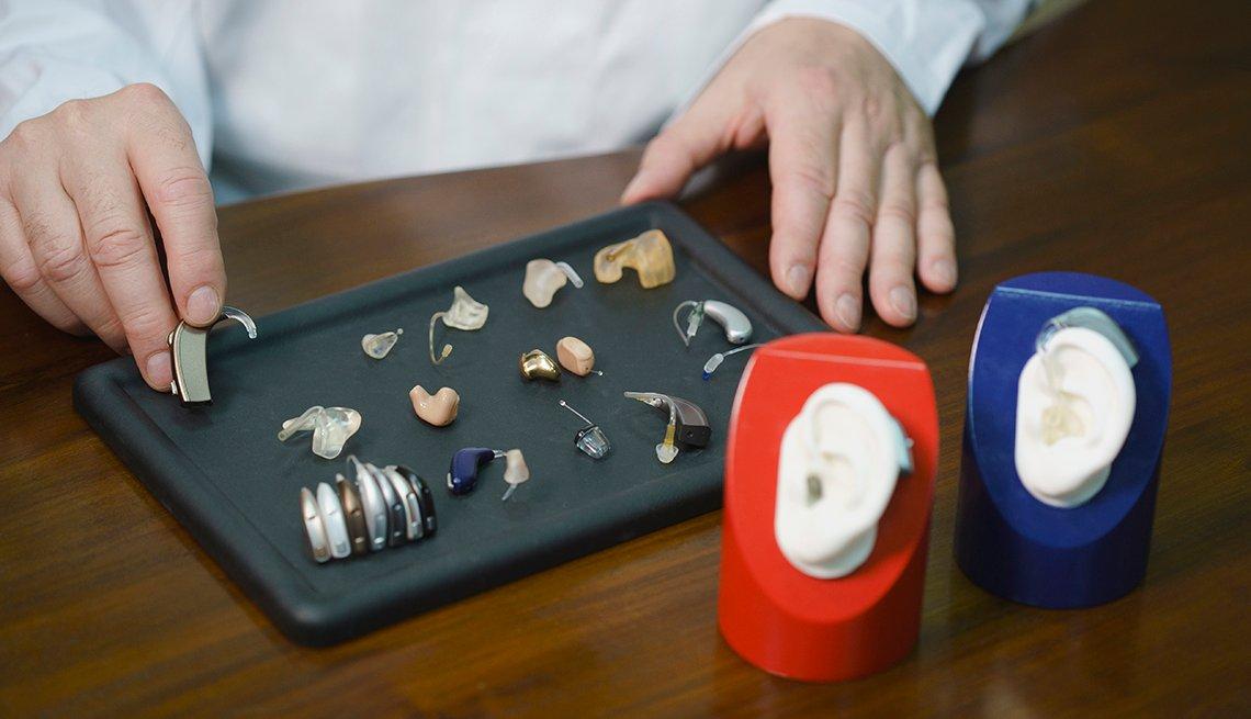 Manos de un médico que muestran diferentes tipos de audífonos