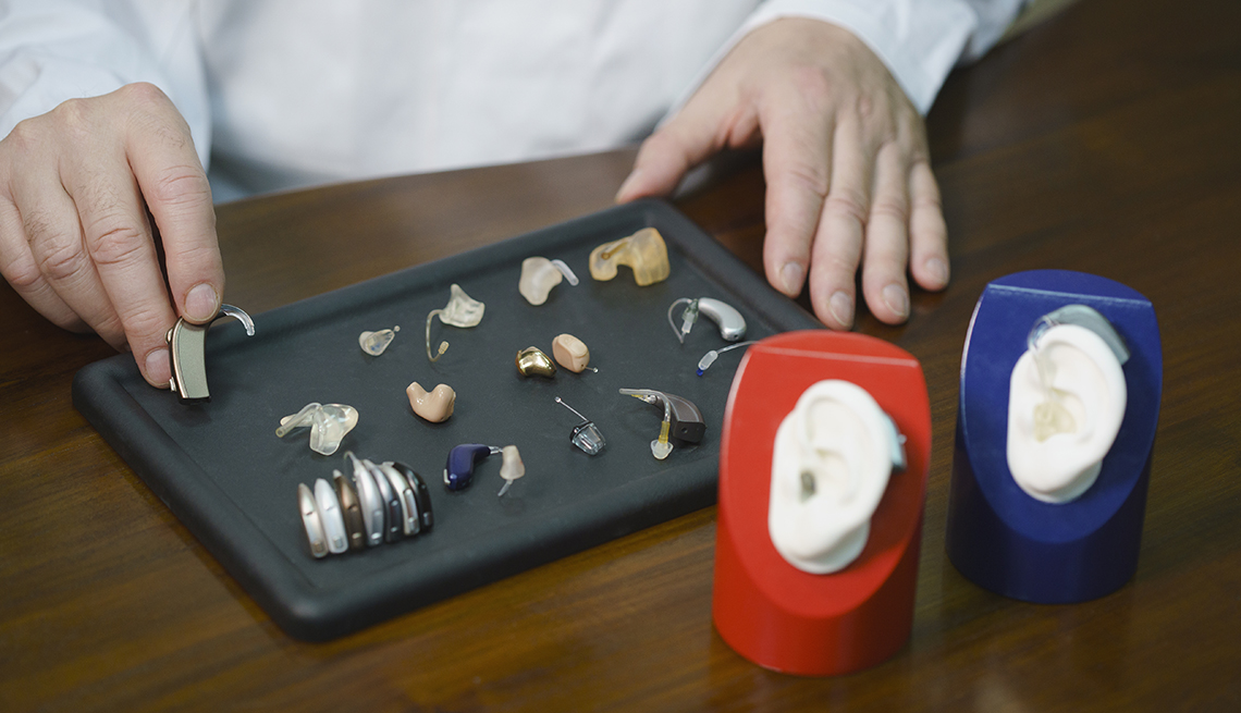 A doctor's hands showing a sample of a hearing aid. Other hearing aids on display.
