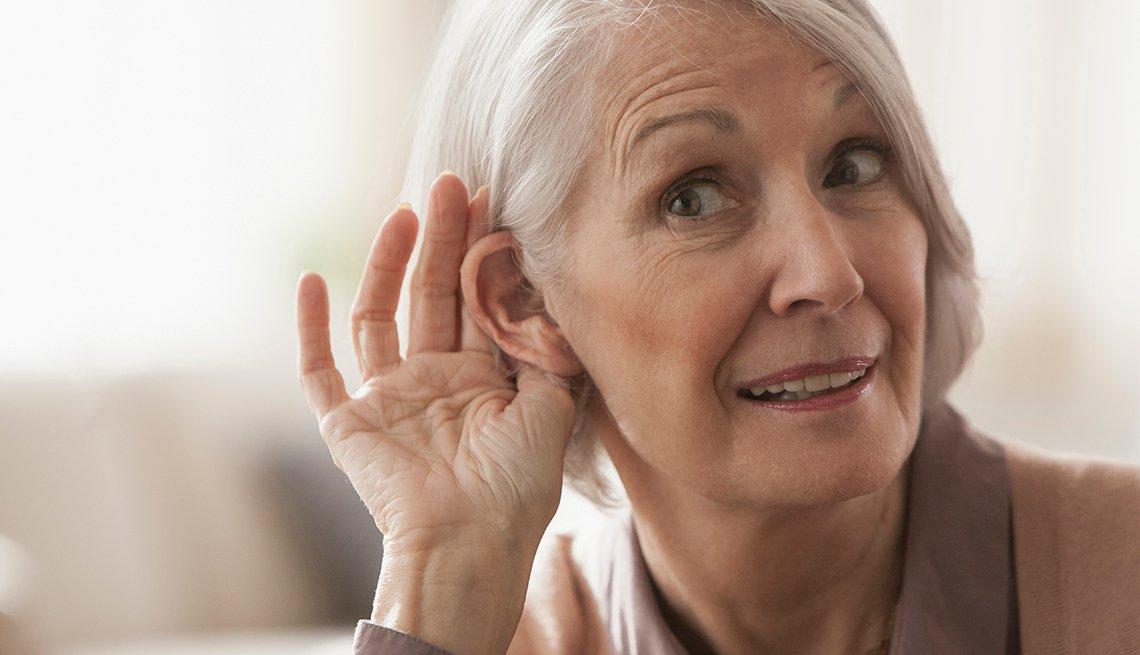 Una mujer lleva su mano al oido para escuchar mejor