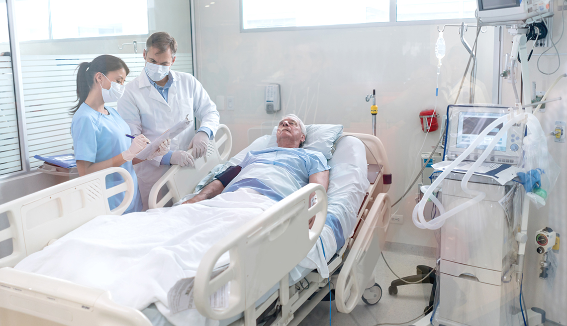 Doctors discussing a patient's case at his hospital bed.