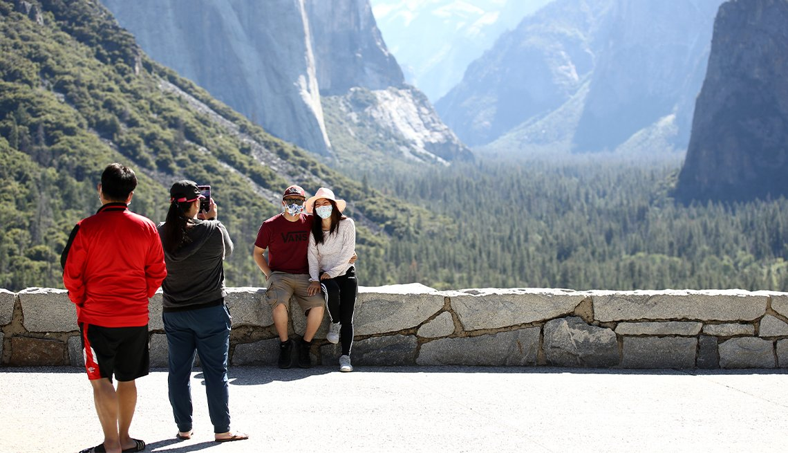 a couple poses for a photograph at a scenic overlook at yosemite national park in california