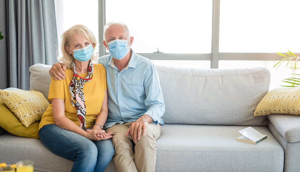 Content couple sitting on their couch with face masks on.